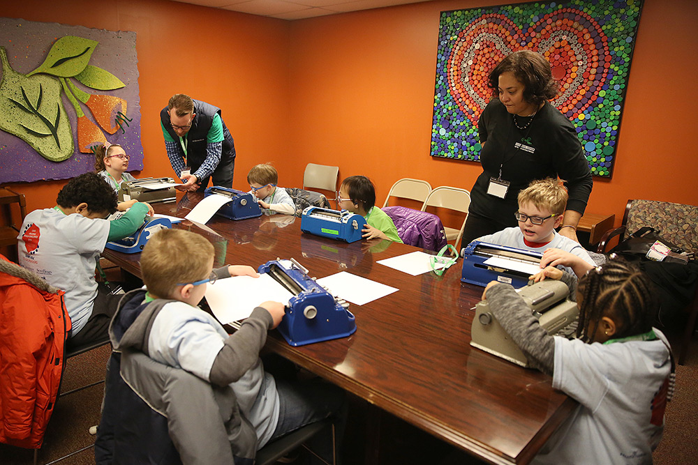 Young students participate in the Ohio Regional Braille Challenge braille explorers activities with volunteers.