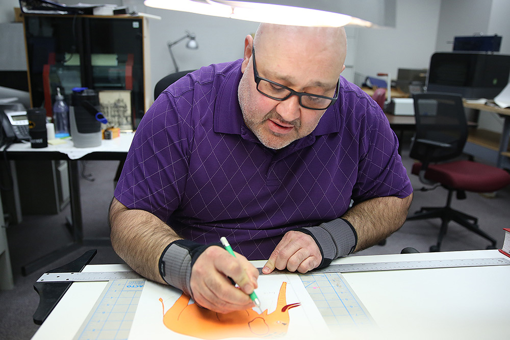 man drawing tactile graphics for Clovernook Center