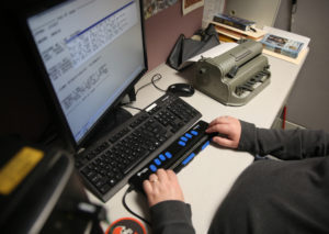 Clovernook Center employee uses refreshable braille display to transcribe text.
