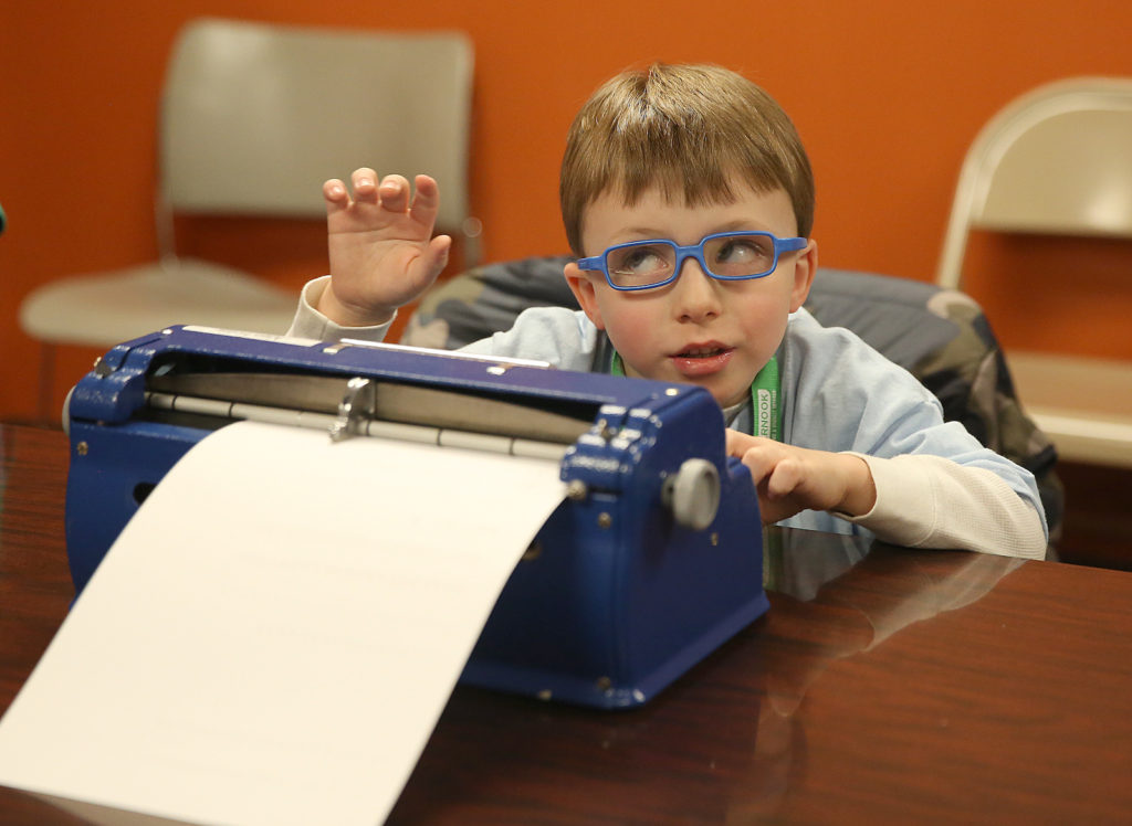 A young student practices using his brailler during the Braille Explorers session.