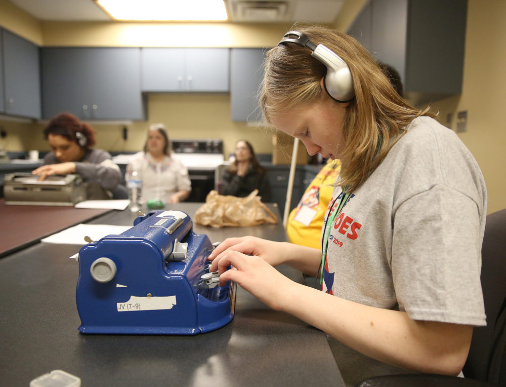 A student competes in one of five skills contest at the Ohio Regional Braille Challenge, working on her Brailler to accurately transcribe an audio recording.