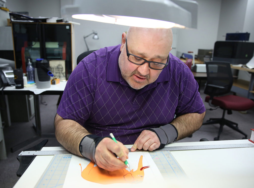 A Clovernook Center employee carefully produces a tactile graphic of an elephant by hand.