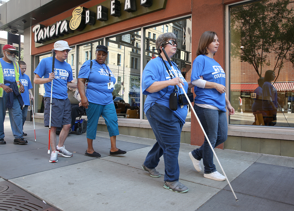 Clovernook Center for the Blind & Visually Impaired employees, both sighted and BVI, use white canes to navigate Cincinnati streets to celebrate White Cane Awareness Day.