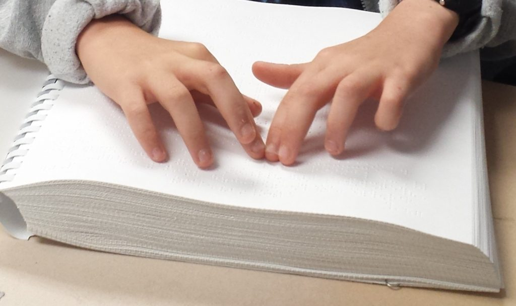 Photo of child's hands as they read braille