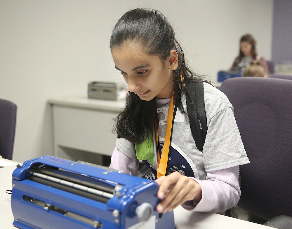 Girl typing on a brailler