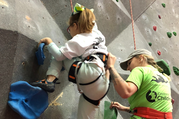 Photo of Adelle rock climbing with the assistance of an aid