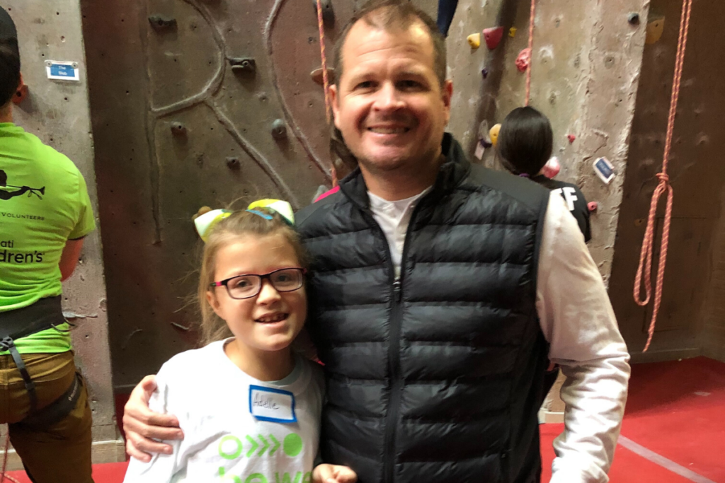 Photo of Adelle and her dad in front of the rock wall