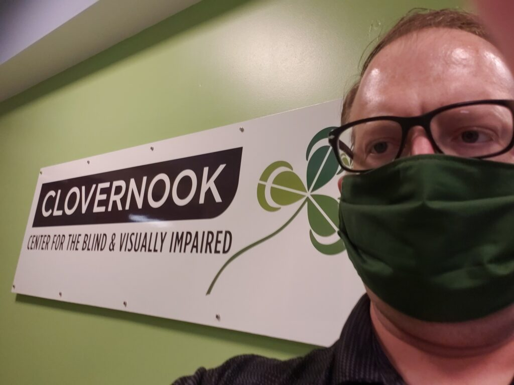 Photo of Isaac standing in front of a Clovernook Center sign wearing a green mask and glasses