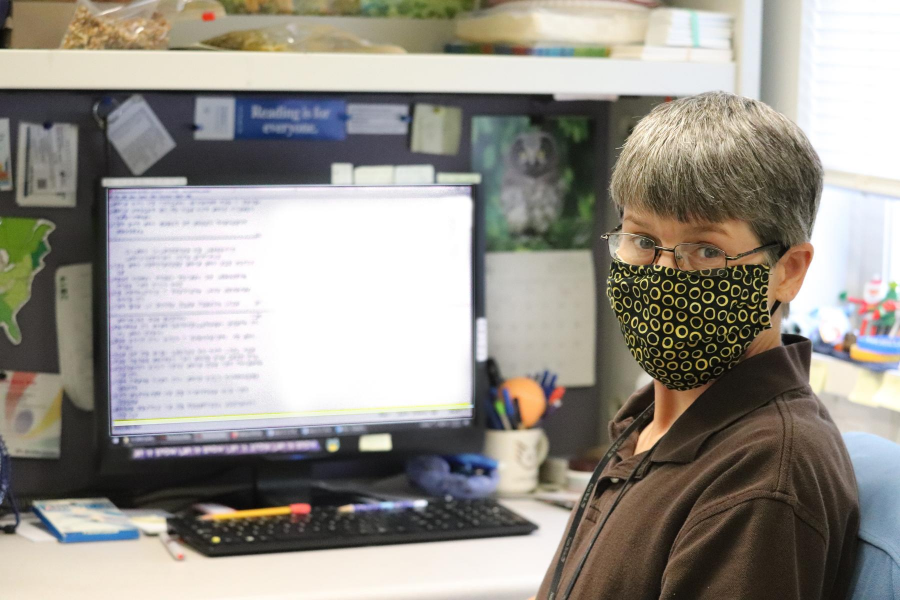Photo of Clovernook Center employee sitting in front of her computer as she transcribes braille