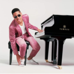man in pink suit sitting at piano